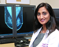 Dr. Chopra at desk with breast images on computer monitors.